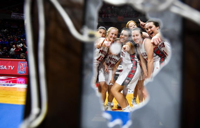 The Morton girls basketball team looks through the Class 3A state championship trophy at Redbird Arena in Normal after winning the 2019 crown — its fourth title in five seasons.