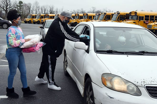 James Rosa, co-founder of the Rosa Foundation with wife T'ebony, and helper Tiffany Durham hand out new winter coats during a drive-through event Saturday at Contentnea-Savannah K-8 Schools. The Rosa Foundation donated 200 new coats for LCPS elementary schools to distribute to students based on need. [CONTRIBUTED PHOTO]