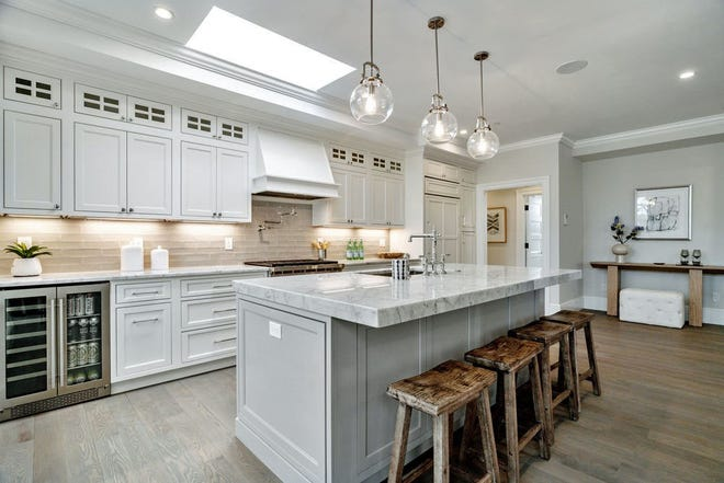 A Carrara marble island with a deep stainless steel sink, classic chrome faucet, a paneled-in dishwasher, Bosch microwave and semi-globe pendant lights initiates the open kitchen, brightened by a skylight. Running parallel to the island is a matching marble wall counter encompassing a subway-tiled backsplash, a Wolf six-burner gas range with pot-filler, a wine cooler and paneled white cabinetry.