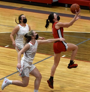 Monroe's Olivia Bussell glides to the hoop on a fast break past Payton Pudlowski and Kerstin Nadolny of Bedford Monday, March 1, 2021.