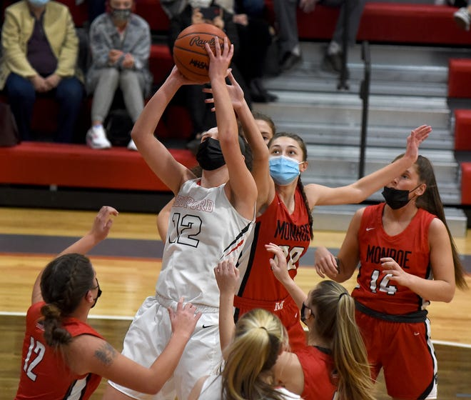 Molly Koviack of Bedford puts up a rebound to score as Anna Sneider of Monroe attempts to stop the shot Monday night. Other players for Monroe are Maycee Pawlicki and Kallie Trouten.