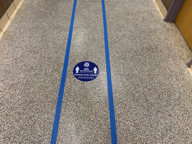 A sign on the floor of Framingham High School encourages social distancing.