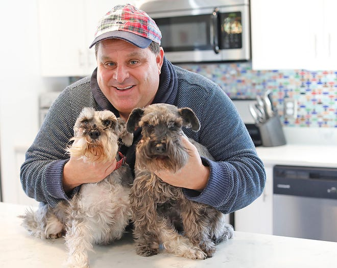 David Giagrando poses in his Weymouth home with his dogs, Wilson and Tucker, on Tuesday March 2, 2021. Giagrando recently joined the Greater Boston Food Bank as Senior Director of Development.