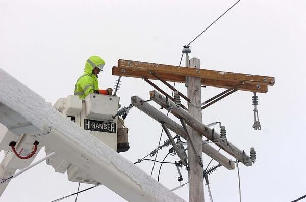 A National Grid worker works on a utility pole.