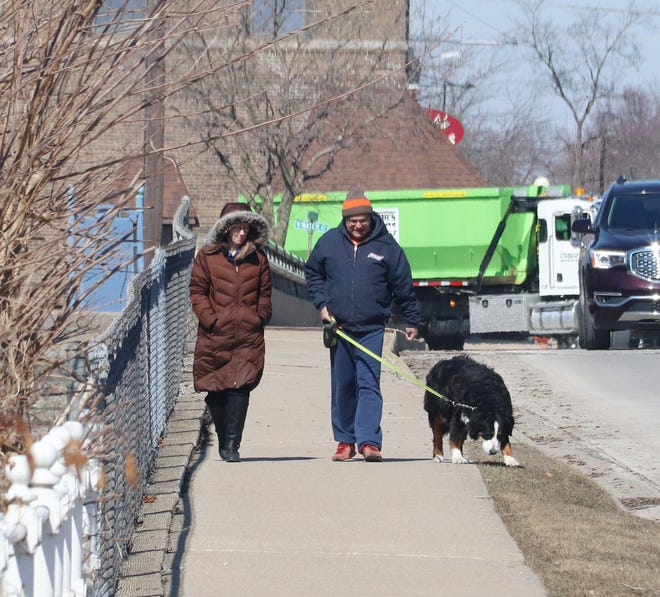 Tuesday afternoon was a bit chilly, but the sun was shining to make a nice day for a walk in downtown Pontiac. This couple took advantage of the weather and had a stroll with their dog across the Vermilion River Bridge on Mill Street.