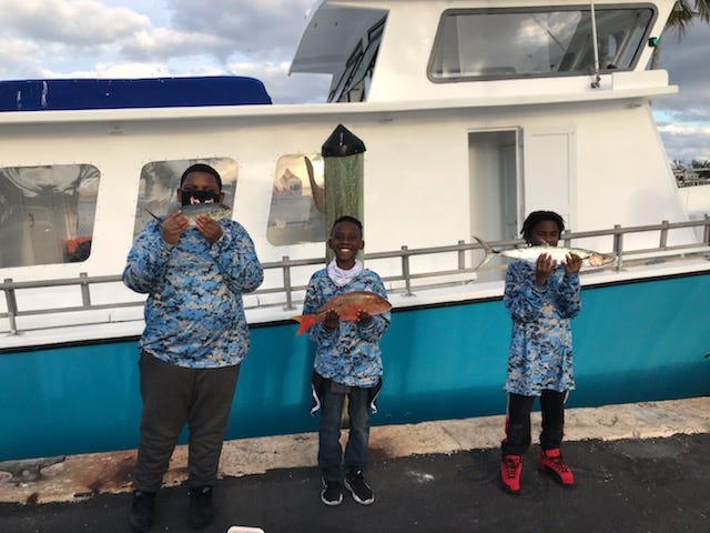 Robert Janque, Kanyen Gross and Isaiah Roseme hold their catches during the fishing tournament sponsored by American Academy in January.