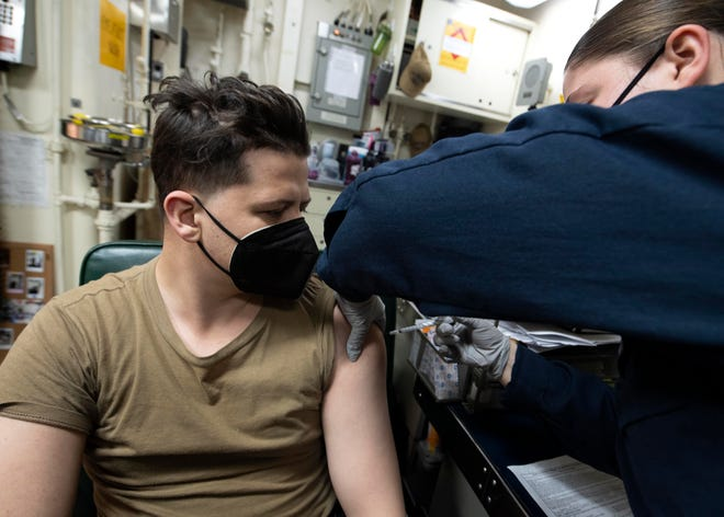 Hospital Corpsman 3rd Kaitlyn Dublin, right, administers the COVID-19 vaccine to Machinist's Mate Seaman Rowan Hayes in the USS Iwo Jima medical department on Feb. 19.