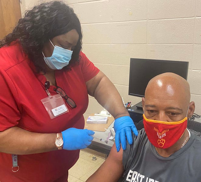 Constance Johnson administers the COVID vaccination to East Iberville School principal Hiram Wade Bailey.