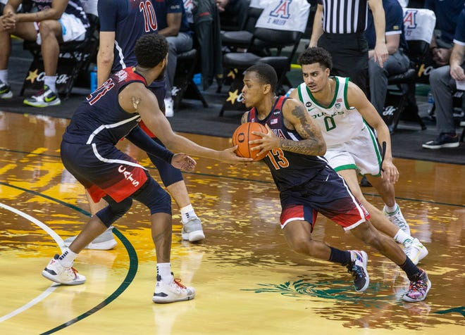 James Akinjo (13) takes the ball in a hand off from Jordan Brown (21) with Oregon Will Richardson (0) hot on his heels. Oregon men's basketball hosts the University of Arizona on Monday, March 1, 2021 at Matthew Knight Arena in a make-up game originally scheduled for Jan.16.