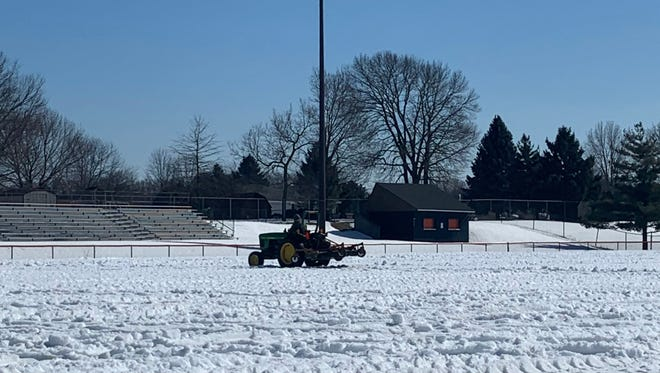 A maintenance worker attempts to break up some of the ice on the Harlem High School football field on Tuesday. Harlem has one of the highly sought-after turf fields in the area.