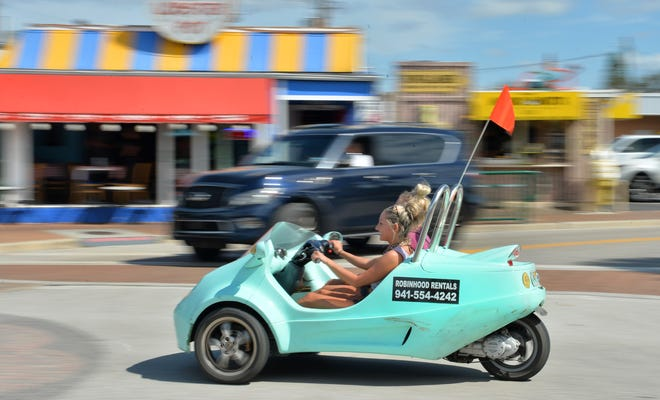 Sarah Beauleau and Ari Brust, both visiting Siesta Key from Stanford, Connecticut, cruise down Ocean Boulevard in a rented scooter car in Siesta Key Village on a recent Friday afternoon.