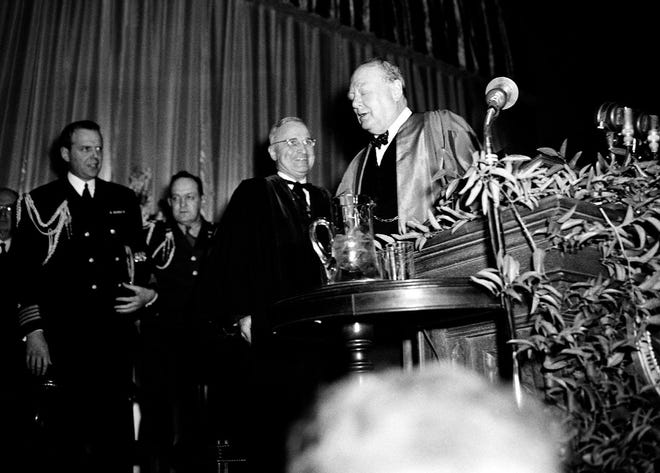 Winston Churchill, guest speaker at Westminster College, March 5, 1946 in Fulton, Mo., turns to President Truman, who introduced him. Aides of president are at left.