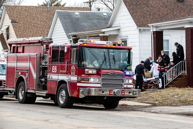 Members of the Springfield Fire Department help load a patient onto a stretcher while assisting paramedics after being first to the scene on a medical call on East Laurel Street in Springfield, Ill., Friday, February 26, 2021. [Justin L. Fowler/The State Journal-Register]