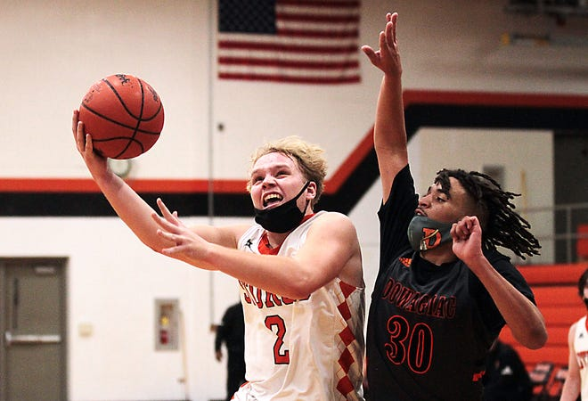 Brady Webb of Sturgis puts up a running hook around the defense of Stewart Smith of Dowagiac on Monday evening. The shot went in for two points.