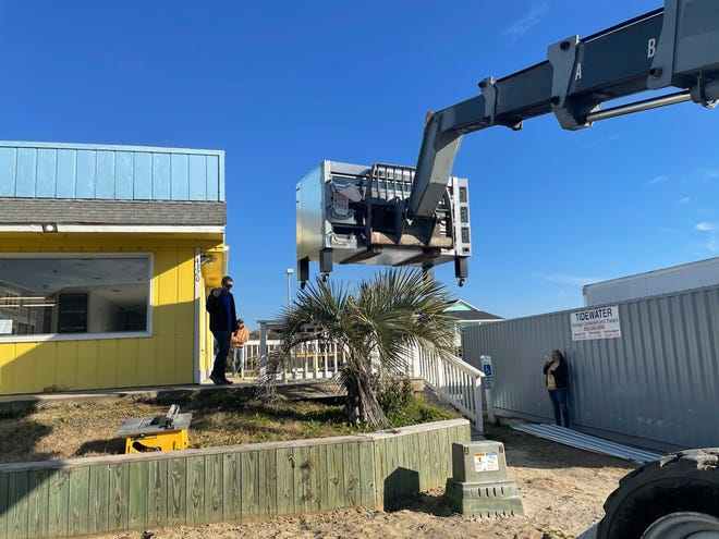 A new pizza oven is lifted in at Pepperoni Grill at the Beach in Oak Island.