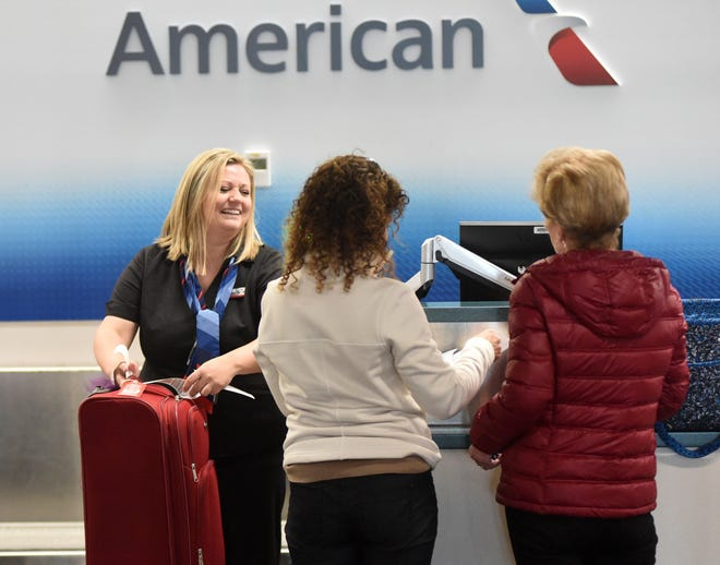 American Airlines Customer Service Agent Heather Berls, left, checks in customers at Wilmington International Airport in Wilmington, N.C., Friday, March 1, 2019.
