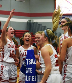 Ballard's Brooke Loewe (left), Paige Noe (center), Sydney Briggs and Josie Fleischmann celebrate with their teammates as Noe holds up their Class 4A state qualifier banner after a 55-35 victory over North Polk in in the regional finals Feb. 23 at Huxley.