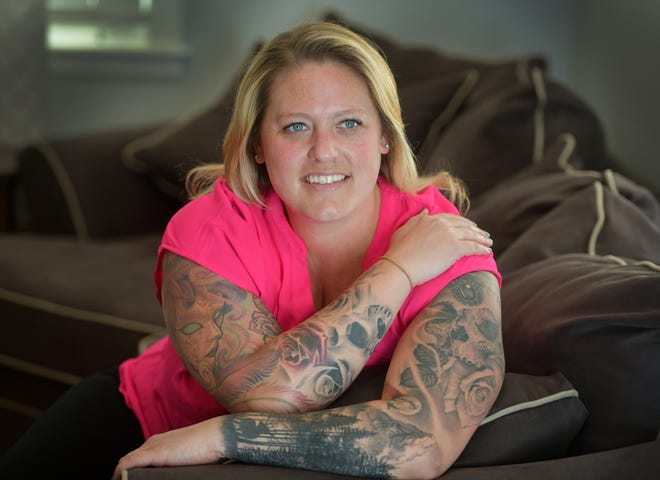 Lindsey Bartlett shows her arm tattoos Tuesday at her home in Worcester.
