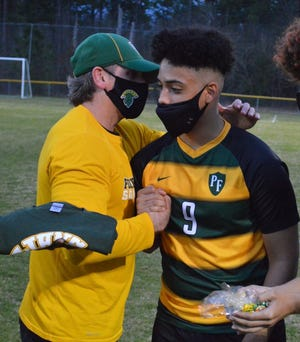 Pine Forest coach Isaac Rancour embraces senior defender Christian Flerlage, who helped the Trojans earn a 2-1 win against Gray's Creek on senior night to improve their record to 6-0-1.