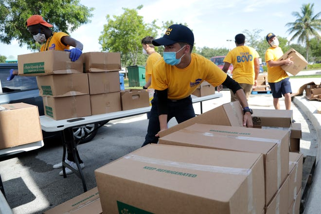 Nicholas Martinez stacks boxes of produce at a free drive-through food distribution by Farm Share at St. Monica's Catholic Church on July 7 in Miami Gardens.