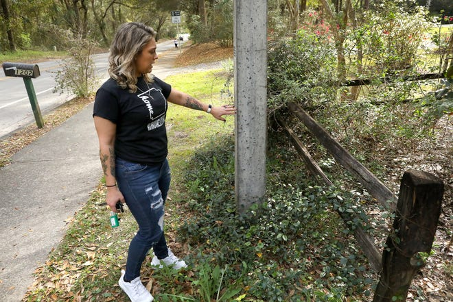 Nicky Villardefrancos points out a concrete pole her son Nathaniel, 8, was launched into when he and his brother Lucas, 10, were hit by a car on their way to school last week, off Northwest 38th Street near Littlewood Elementary in Gainesville.