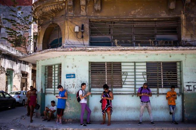 Pedestrians use their smartphones to surf the internet in Havana, Cuba.