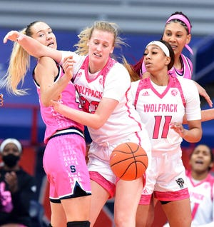 From left, Syracuse Orange forward Digna Strautmane (45), NC State Wolfpack center Elissa Cunane (33) and NC State Wolfpack forward Jakia Brown-Turner (11) vie for a rebound in an NCAA college basketball game in Syracuse N.Y., Feb 28, 2021. (Dennis Nett/The Post-Standard via AP)