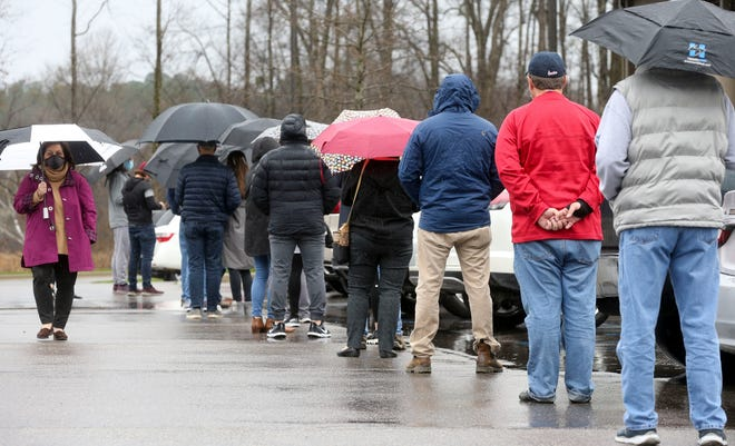 A line of voters wait beneath umbrellas to enter the District 3 polling place at Church of the Highlands to vote in the Tuscaloosa municipal elections on Tuesday. District 3 had the largest single-district turnout percentage with 32% as 3,908 of the 12,248 registered voters for the district cast votes. [Staff Photo/Gary Cosby Jr.]