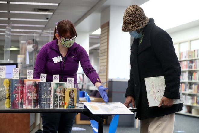 Alexandria Carter, information services manager, helps Janet Smith of Whitehall find materials Feb. 25, at the Reynoldsburg branch of the Columbus Metropolitan Library. Opened in 1980 at 1402 Brice Road, the 19,800-square-foot library is the oldest CML branch in use. A new 37,500-square-foot branch is expected to open in 2023.