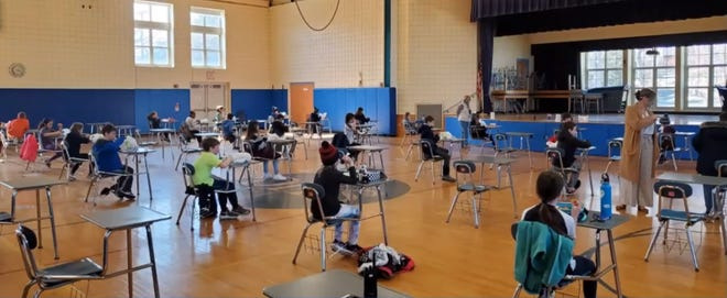 Deer Hill School students eat lunch while socially distanced inside the schools gymnasium.