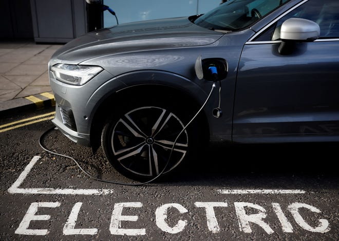 In this file photograph taken on Nov. 18, 2020, a charging cable hangs plugged into a Volvo electric vehicle (EV), parked in a parking bay reserved for electric vehicles in London. Chinese-owned Swedish automaker Volvo said March 2, 2021, that it will produce only electric vehicles by 2030 and sell them all exclusively online. Volvo is among a growing crop of companies planning to ditch fossil fuel vehicles in the next few years, as demand for zero-emission cars rises and governments put pressure on firms to cut pollution.