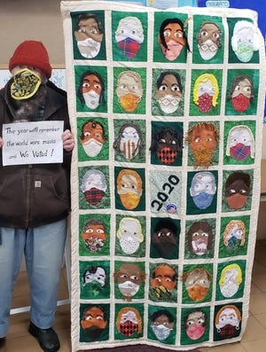 A masked Margaret Naysmith stands with the quilt she made depicting faces of different races all wearing masks which is on display at the Algoma Public Library. Naysmith is holding a sign that normally is next to the quilt explaining her idea behind making it.