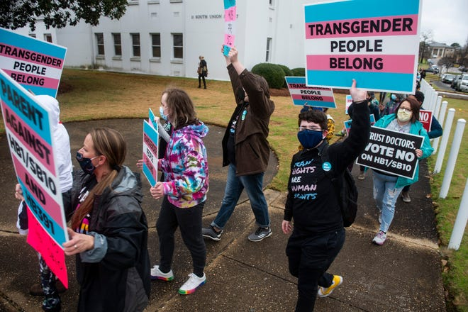 Protesters in support of transgender rights march around the Alabama State House in Montgomery, Ala., on Tuesday, March 2, 2021.