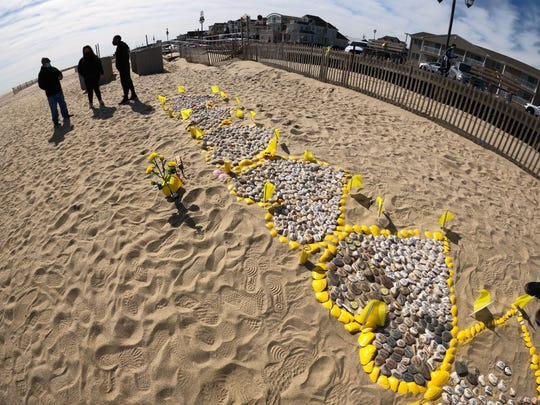 Inscribed stones fill yellow painted shell hearts created by Rima Samman on Belmar's 3rd Avenue Beach Friday, February 26, 2021.  She started it in honor of her brother Rami, who died of COVID last year, has been growing as people from around the world ask names to be added.