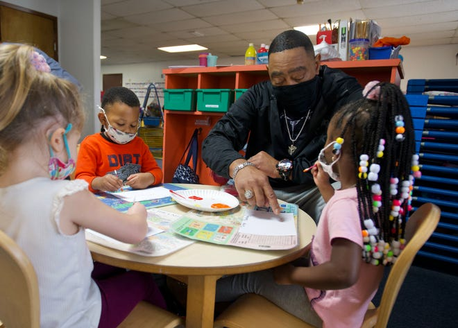 Robert Robinson teaches 2-year-olds their colors while painting pictures Tuesday at House of Prayers Learning Center in Pensacola.