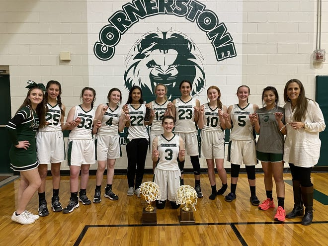 The San Angelo Cornerstone Christian School girls basketball team, led by head coach Lora Bird, poses with its TAPPS Class 1A area-round trophy on March 1, 2021, in the Cornerstone gym.