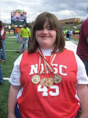 Jenny McGowan shows off her medals at Special Olympics.