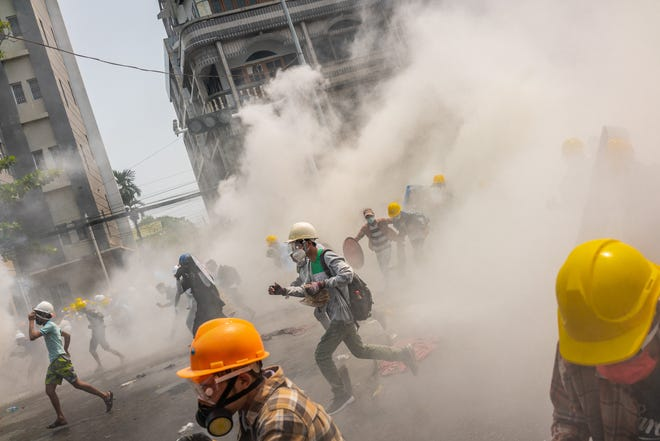 Anti-coup protesters react after riot police fired tear gas to disperse them on March 2, 2021 in Yangon, Myanmar.