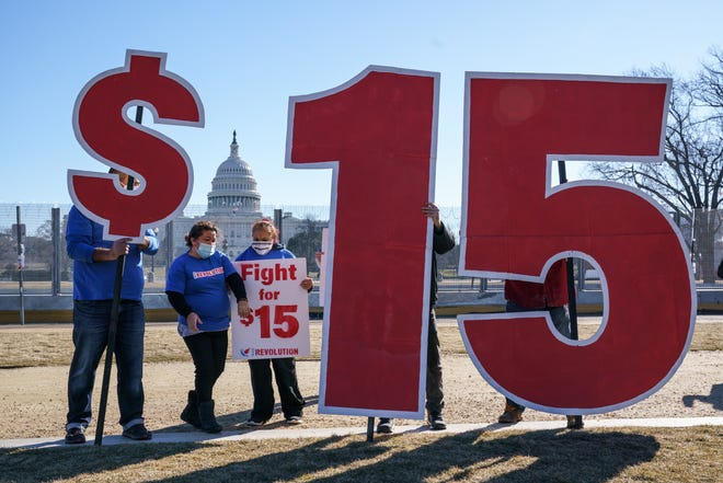 Activists appeal for a $15 minimum wage near the Capitol in Washington, Thursday, Feb. 25, 2021. The $1.9 trillion COVID-19 relief bill being prepped in Congress includes a provision that over five years would hike the federal minimum wage to $15 an hour. (AP Photo/J. Scott Applewhite) ORG XMIT: DCSA103