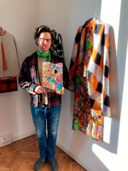 Milan-based Austrian fashion designer Arthur Arbesser, poses in his studio holding a painter's pallet that he picked up at a flea market, and which inspired the signature print for his Fall 2021 collection of 25 looks, in Milan, Italy, Sunday, Feb. 28, 2021.