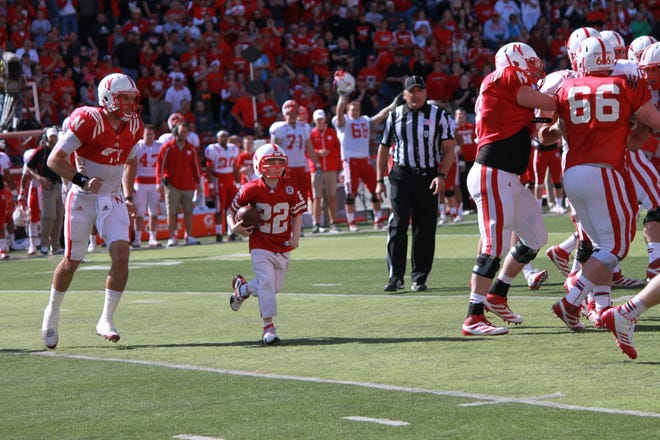 Seven-year-old Jack Hoffman, center, runs for a touchdown during a special segment of the Nebraska Red-White Spring Game in 2013.