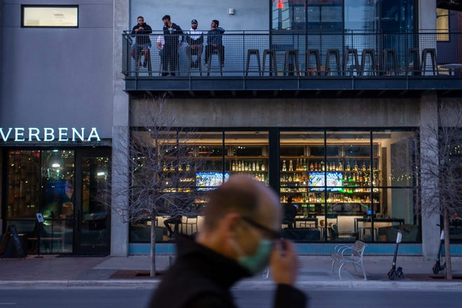 People drink on the upper level of Verbena as a man walks past on Tuesday, March 2, 2021 in Austin, Texas. Texas Gov. Greg Abbott rescinded the state wide mask mandate Tuesday afternoon with plans for businesses to open at 100 percent capacity next week.