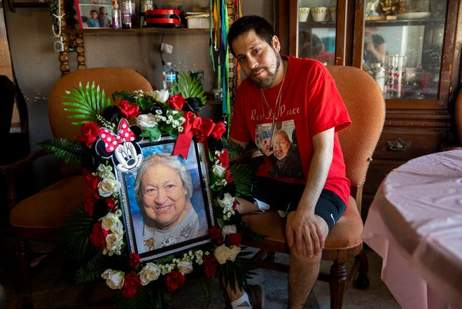 Miguel Rangel, 30, sits for a portrait next to a photo of his mother, Diana Martinez Rangel, 71, while at their home in Manor on March 2. Daniel died Feb. 19 as millions of Texans were without power, heat and water after a winter storm slammed into the state. Her family believes she died after having missed two dialysis appointments when the clinic was closed due to the storm.