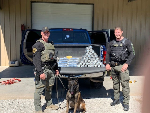 Fayette County Sgt. Randy Thumann, Kolt, and Deputy Jeremy Ellison are pictured with drugs found during a March 2, 2021 traffic stop.