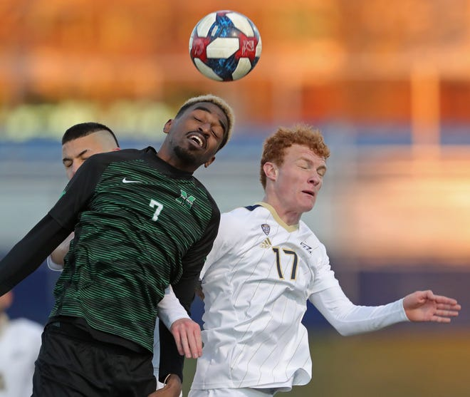 The University of Akron's Ryan Combe, right, makes a play for the ball against Marshall's Milo Yosef during a game earlier this season. The Zips have postponed one game and canceled another this week to conduct contact tracing after a positive COVID-19 test. [Jeff Lange/Beacon Journal]