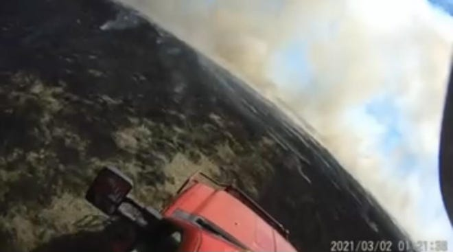 Helmet camera footage from Lane Murphy with the Enville Fire Department shows heavy smoke south of the Marietta High School football field Tuesday, March 2, 2021.