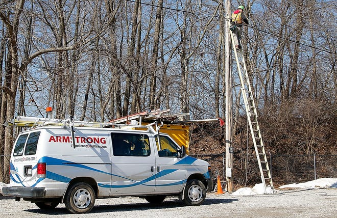An Armstrong employee works on reinstalling a cable wire that was pulled down at Bo Lacey Construction's showroom on U.S. Route 42 on Wednesday. Armstrong provides cable and internet services for much of Ashland County as well as the city of Orrville and the village of Dalton in Wayne County.