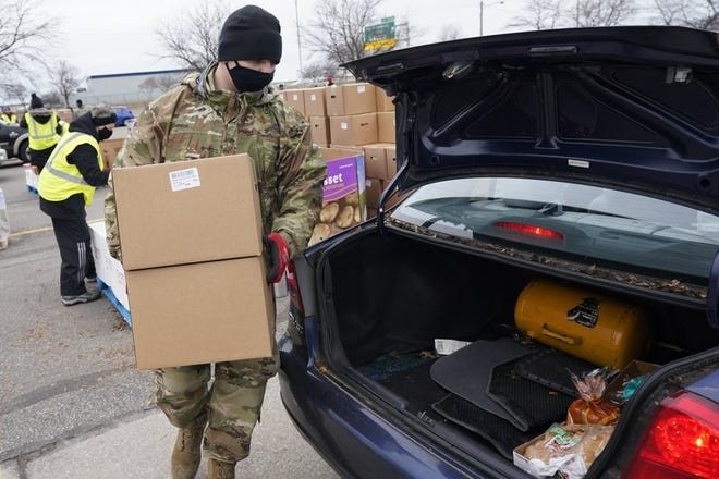 Staff Sgt. Mike Schuster loads two produce boxes into a car at a food bank distribution by the Greater Cleveland Food Bank, Thursday, Jan. 7, 2021, in Cleveland.