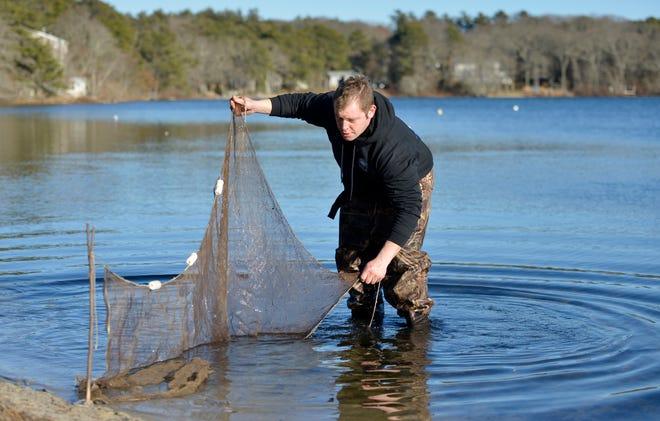 Dan Hannigan demonstrates how he uses a net to capture bait fish.