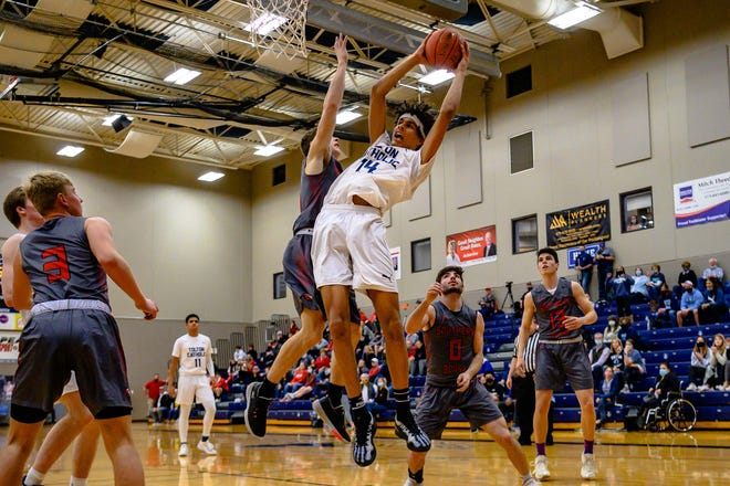 Tolton's Jevon Porter (14) pulls down an offensive rebound against Southern Boone during a Class 4 District 8 semifinal Tuesday night at Tolton High School.